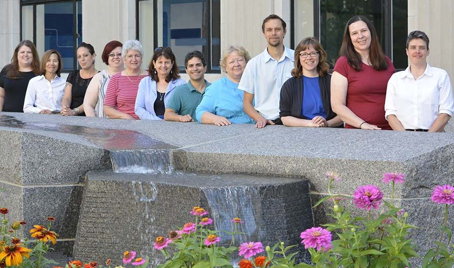 HSC Staff Members standing behind the fountain on the Ithaca Commons