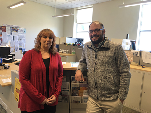 Dawn Sprague and Rodney Maine pose at the COFA front desk