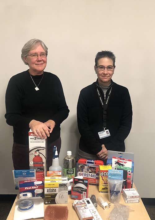 Pat and Diana pose in front of giveaway items at the Tompkins County Health Department