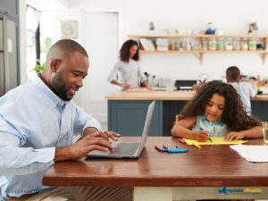 Man in kitchen at laptop looking at health insurance options while family works in background