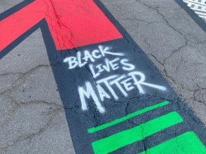 """Painted sidewalk reading """"Black Lives Matter"""" as part of an anti-racism mural in Ithaca NY"""
