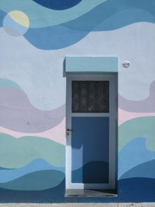 A wall painted blue and purple with a door to housing initiatives